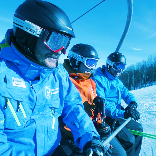 A group of snow sports school students on a chair lift.