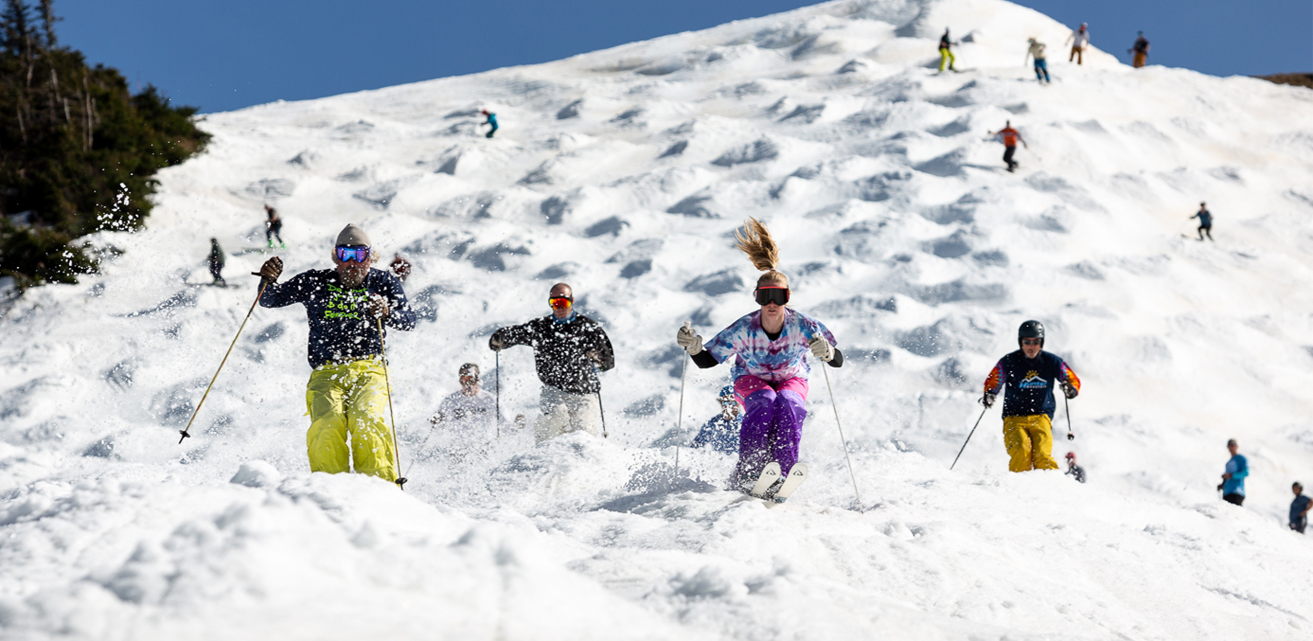 Large group of spring skiers charging down a mogul filled Superstar trail at Killington Resort