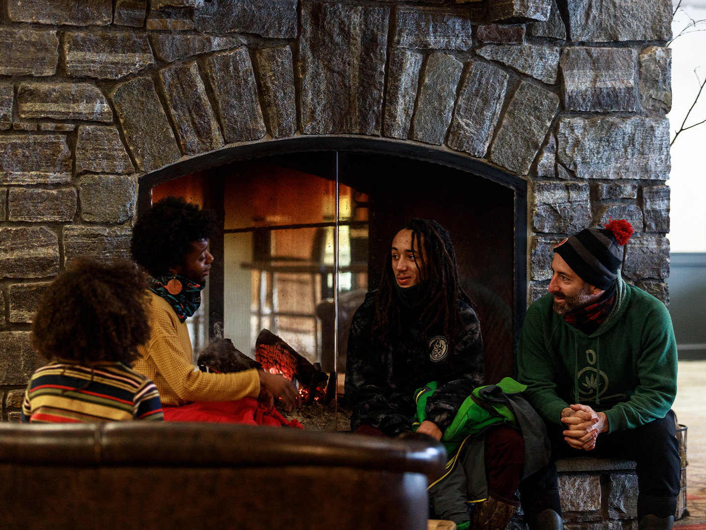 Family enjoying the warm fire at the Killington Grand Hotel while lodging on resort with a ski and stay package